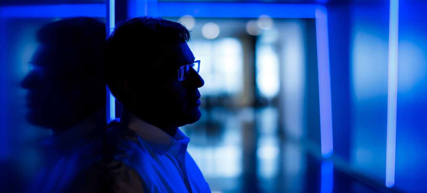 A portrait of Amazon's Rohit Prasad, vice president and head scientist of Alexa Machine Learning. Prasad is bathed in blue light.