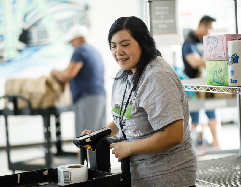 Erika Lopez holds a scanner and stands behind a cart during a shift at the Prime Now facility in Seattle, Washington. Two co-workers are visibile in the background.