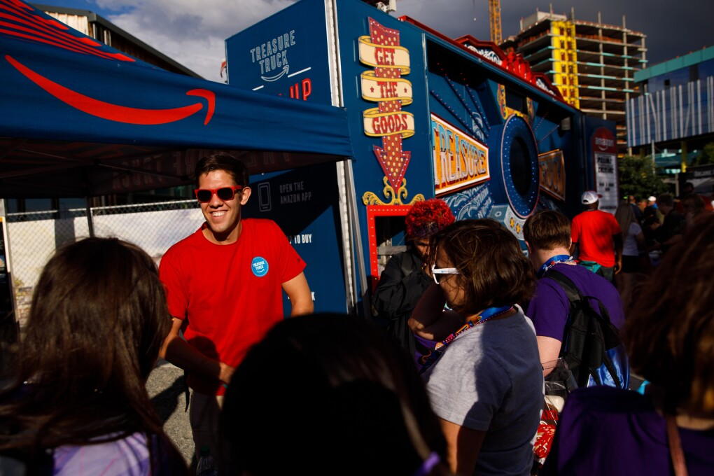 A man in a red tee shirt and sunglasses works at the Treasure Truck, handing out exclusive trading pins to athletes at the closing ceremony. The Treasure Truck is surrounded by people wearing Special Olympics clothing and lanyards.