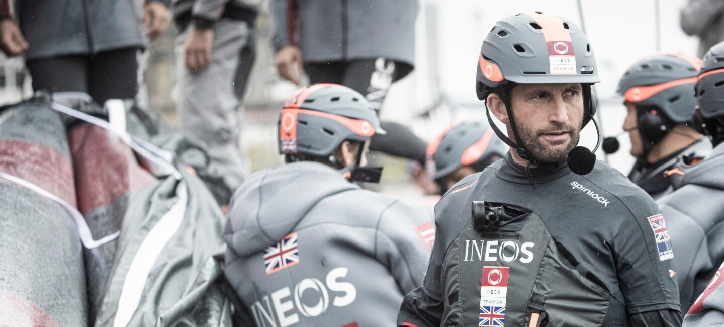 The INEOS Team UK team in their branded sailing gear.  Sir Ben Ainslie, who leads the team is a the front of the picture.