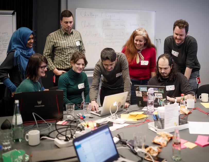 Junge Leute arbeiten zusammen an einem großen Tisch mit mehreren Laptops