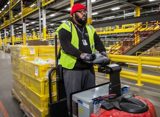An Amazon employee drives a forklift pulling shrink-wrapped containers in an Amazon Fulfillment center to showcase workplace safety in Fulfillment centers