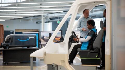 Amazon Fahrerin Natasha Riggins sitzt auf dem Fahrersitz des Fahrzeugmodels.