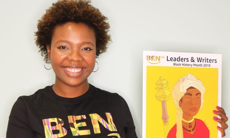 Aisha Suleiman, Executive Board Director of Black Employee Network, holding artwork of Queen Amina
