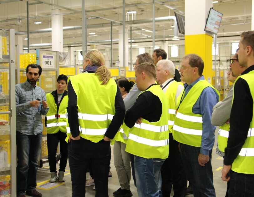 Ali Türk steht vor einer Besuchergruppe und weist auf ein Regal mit gelben Transportbehältern