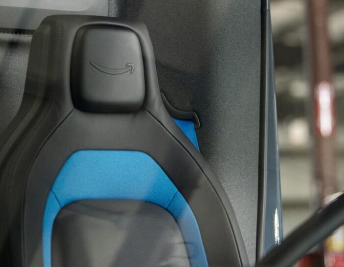 Primo piano del sedile del conducente del furgone elettrico Rivian. Il sedile è nero con un bordo azzurro. Sulla testata del sedile, in rilievo, il logo smile di Amazon