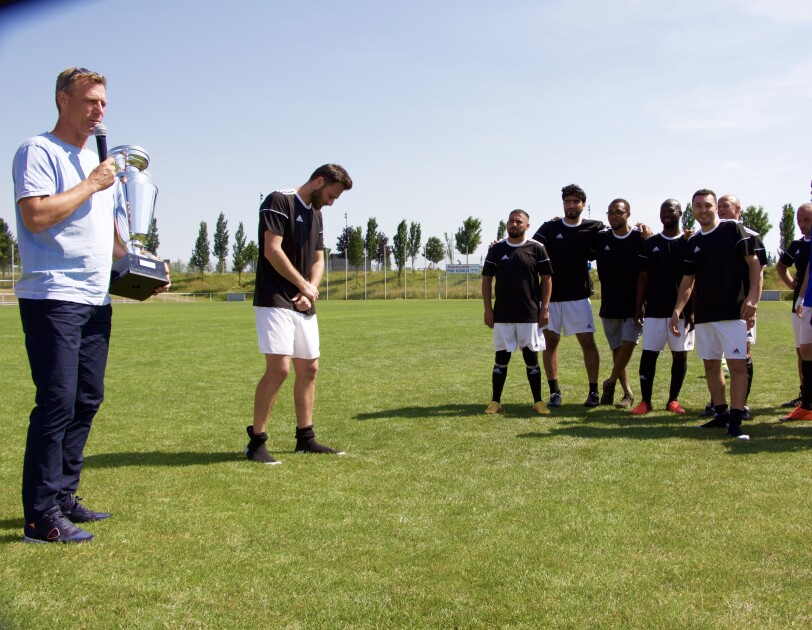 Ein Mann rechts im Bild hält einen Pokal. Um ihn herum versammeln sich Fußballspieler.