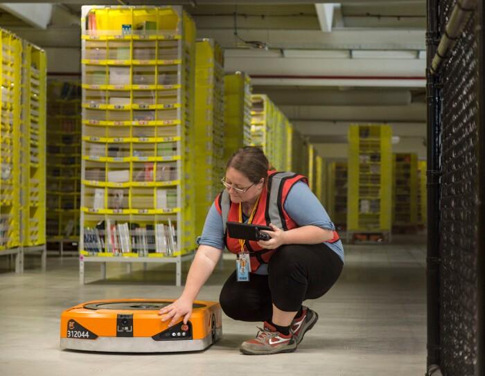 Foto di Maria Stella Carnà che regge un tablet di controllo e si china su uno dei robot di cui è responsabile all'interno del Centro di Distribuzione Amazon di Passo Corese