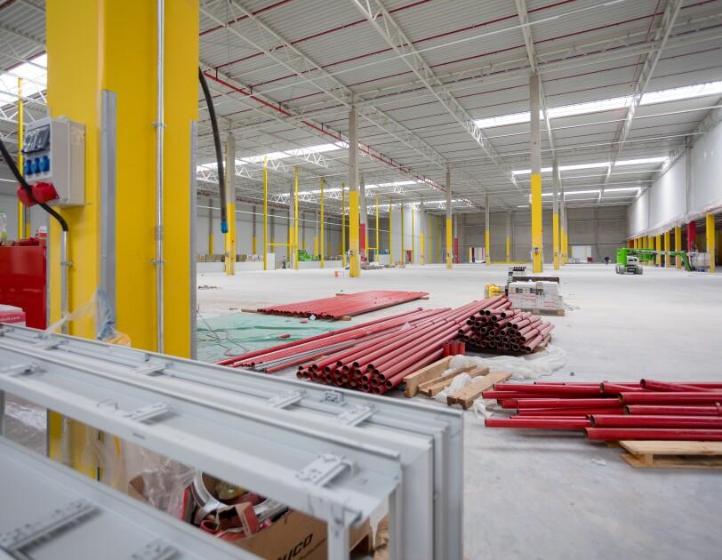 Eine leere weiße Halle mit gelben Stützpfeilern. Auf dem Boden sind zahlreiche rote Rohre gestapelt.