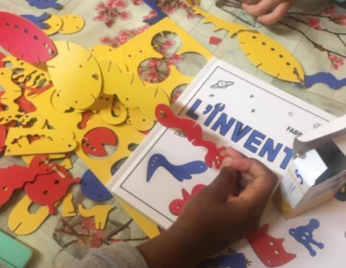 Primo piano di mani di bambini che giocano con ritagli di carta e album da disegno