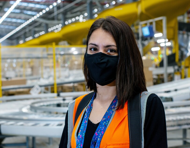 Teodora Halmagean, wearing a facemask and standing in an Amazon Fulfilment Centre in Doncaster.