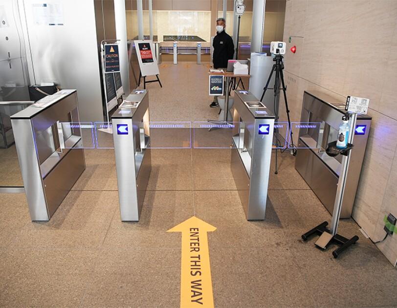 入館ゲートの横に消毒液とサーモグラフィカメラが設置されている。警備員がこちらをみている