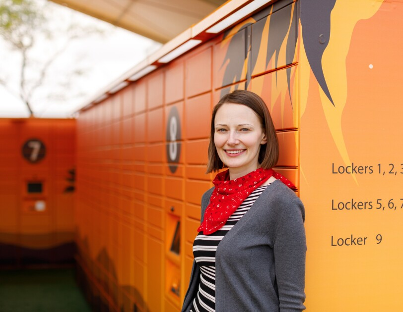 A woman in a sriped shirt, sweater, and a bandanna is photographed from the waist up in front of an installation of Amazon Lockers.