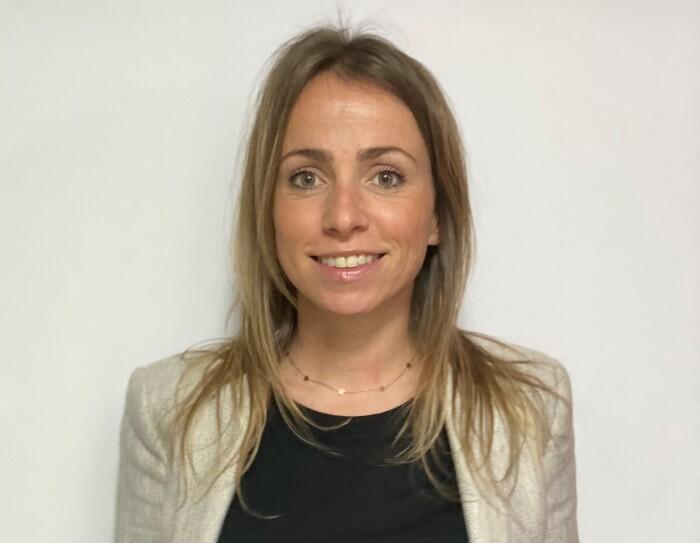 Ana Cruz Dorado, responsable de Recursos Humanos en SVQ1 (centro logístico de Amazon Robotics en Sevilla). Con una jersey negro y una americana gris. Se aprecian unos jeans. El pelo rubio por el hombro y los ojos verdes. Lleva una cadena de oro con estrellas.