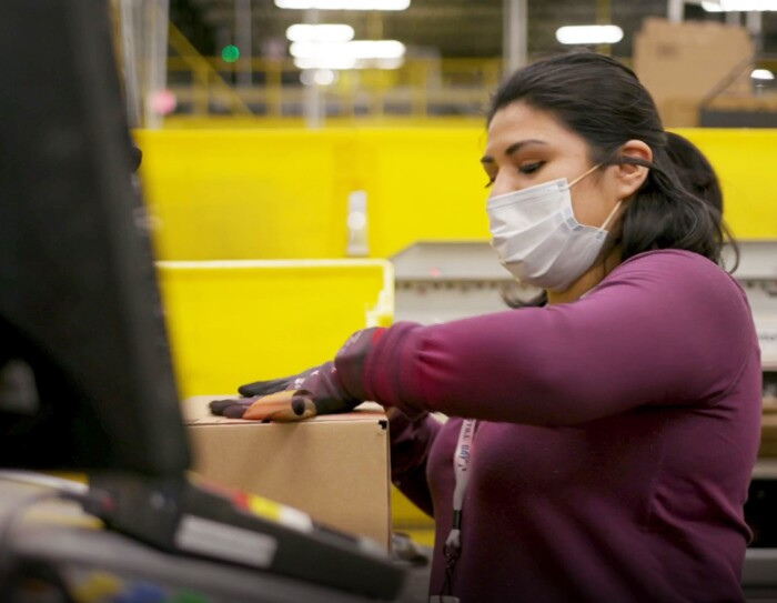 Amazon employee performing work duties while wearing a mask, during COVID-19 pandemic.