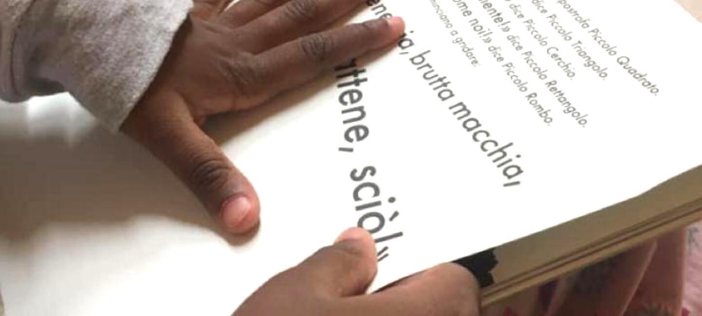 Primo piano delle mani di un bambino che reggono e sfogliano un libro