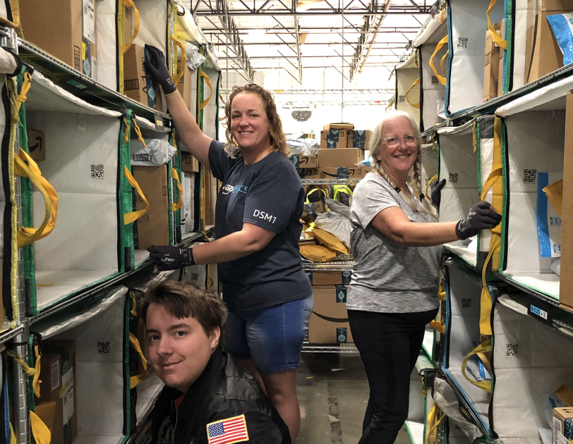 Three individuals working together in an Amazon delivery station.