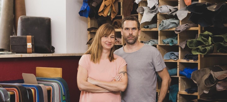 Zwei HAndmade Verkäufer stehen in ihrem Geschäft. Hinter ihnen sieht man ein großes Regal mit den Rohmaterialien für ihr Produkt.