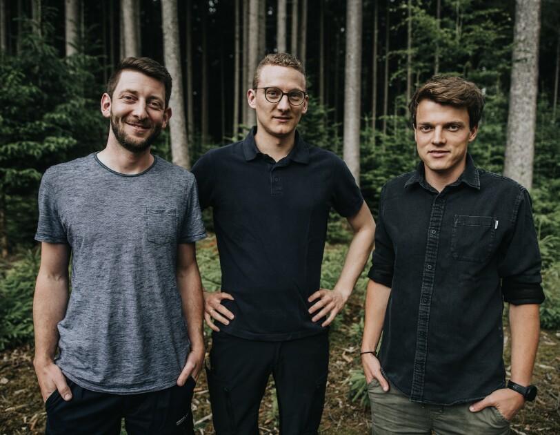 Drei Männer schauen lächelnd in die Kamera. Im Hintergrund sind Bäume in einem Wald zu erkennen.