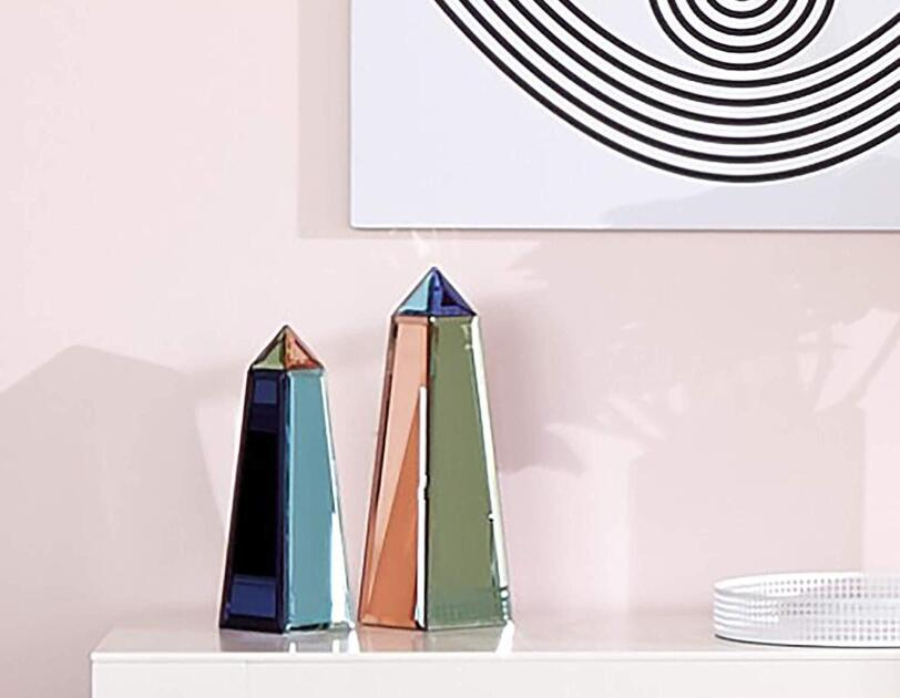 Two multi-color obelisks on a lacquered table. The wall behind the items is soft pink, with a black and white art print depicting an eye.