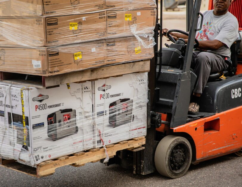 A forklift carries a pallet of goods.