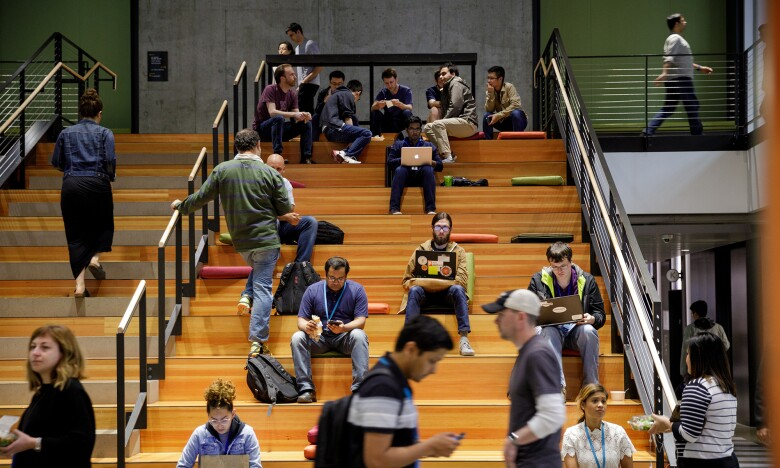 Several Amazon employees sat on a large staircase