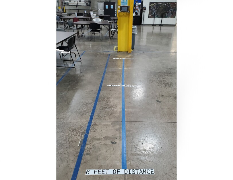 A time clock at an Amazon fulfillment center, with marks on the floor showing where associates should stand while using, and where 6 feet of distance is from the time clock.