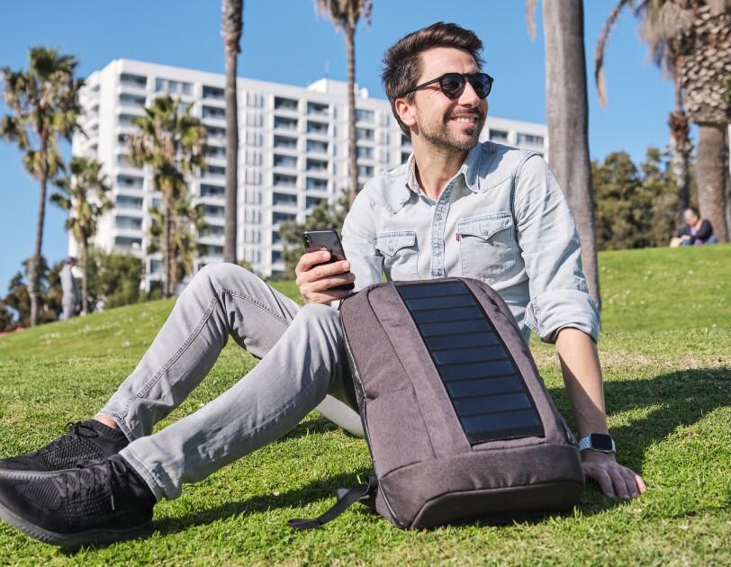 Ein Mann mit braunen Haaren und einem blauen Hemd sitzt auf einer Wiese. Neben sich hat er einen grauen Rucksack mit Solarpannels.
