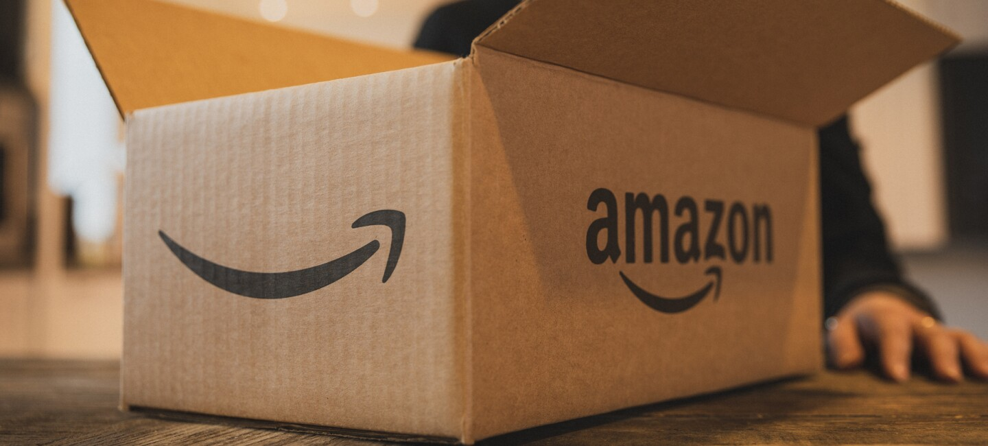 A smiling woman, slightly out of focus, stands behind an open shipping box emblazoned with the Amazon logo, which is resting on her kitchen table.