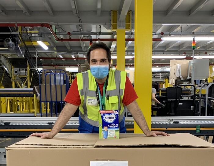Volontario Amazon sorride dietro la mascherina all'interno di un centro di distribuzione. E' poggiato con le braccia su una grossa scatola indirizzata alla Croce Rossa Italiana.