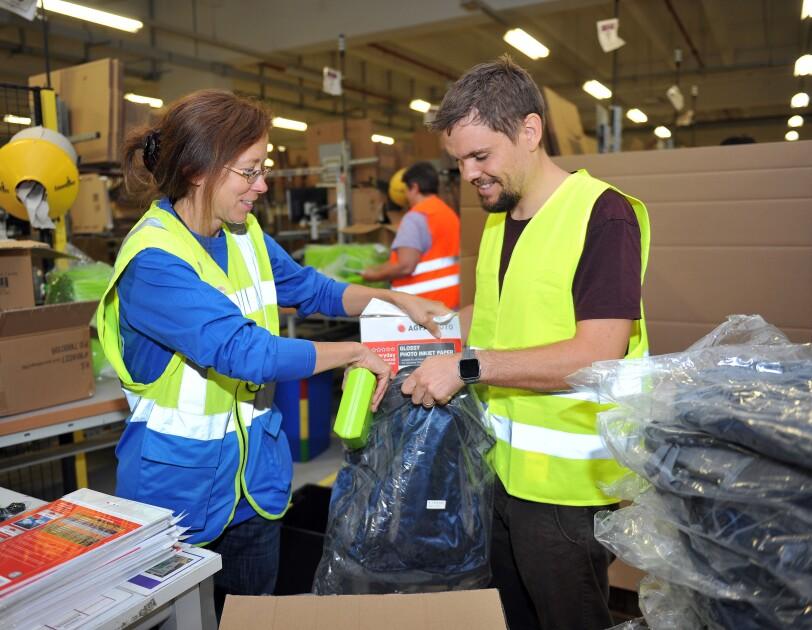 Eine Logistikmitarbeiterin in gelb-blauer Weste packt mit ihrem Kollegen aus der Verwaltung. Er trägt eine gelbe Sicherheitsweste.