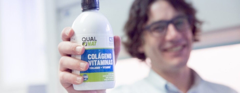 Carmelo Castro de Qualnat mostrando el bote de colágeno. Él, que se encuentra en el laboratorio, esta desenfocado de fondo con una camisa blanca.