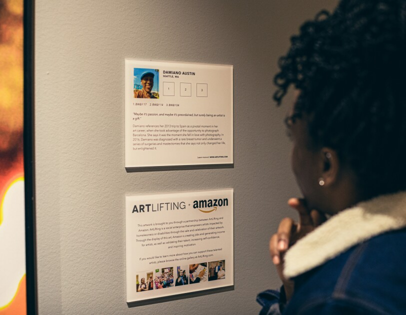 A woman in a blue jacket looks at an artist information card at a gallery.