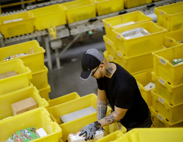 A man stands among yellow plastic tote boxes and handles merchandise. He's wearing a baseball cap, glasses and work gloves, and has tattoos on each arm and his neck.