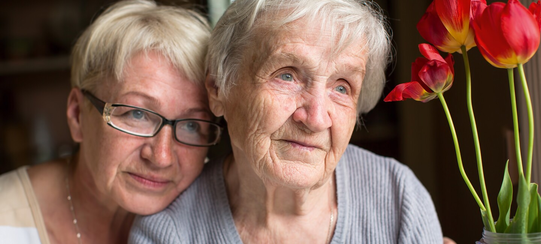 Zwei ältere Damen sitzen am Tisch neben einer Vase mit roten Tulpen.