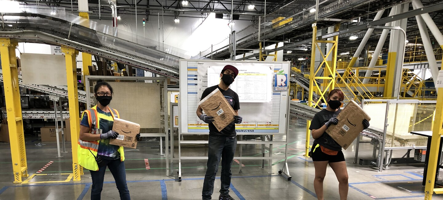 Three Amazon associates stand in a fulfillment center, holding the new recyclable mailer.
