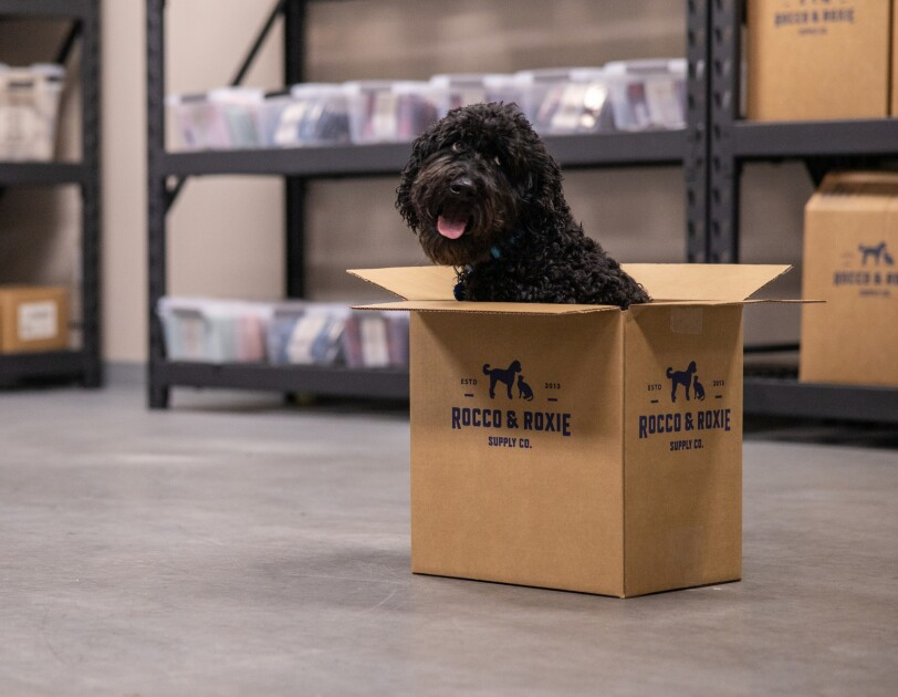 "A dog sits inside a cardboard box labeled ""Rocco & Roxie Supply Co."" The dog's tongue is sticking out. It looks back over its shoulder with its eyes directed up and to the right."