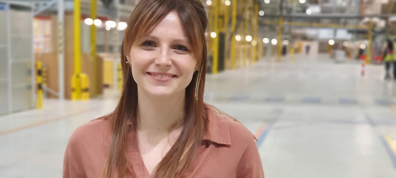Eine junge Frau in Bluse und Jeans steht in einer Logistikhalle