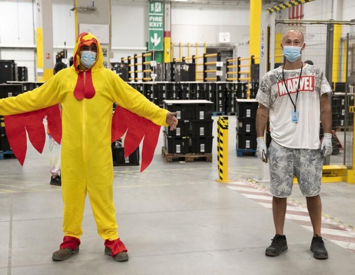 PJammin en MAD6 Illescas. Dentro del centro logístico con las cajas negrad detrás hay dos asociados vestidos en pijama. El de la izquierda va de gallo y el de la derecha con un pijama de manga y pantalón corto de Marvel.