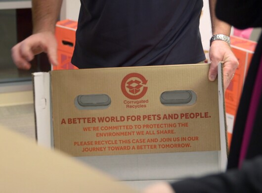 "A panel of a cardboard box marked with the words ""A better world for pets and people. We're committed to protecting the environment we all share. Please recycle and join us in our journey toward a better tomorrow."""