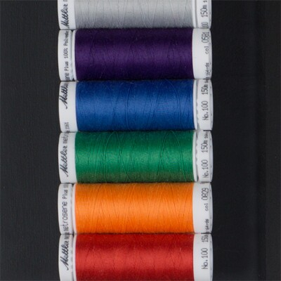 Spools of thread in a range of colors: gray, purple, blue, green, orange, and red.