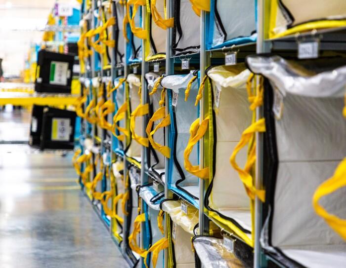 Estantería de un centro logístico con bolsas que tienen las asas de color amarillo. Las estanterías tienen cuatro pisos y más de 10 bolsas.