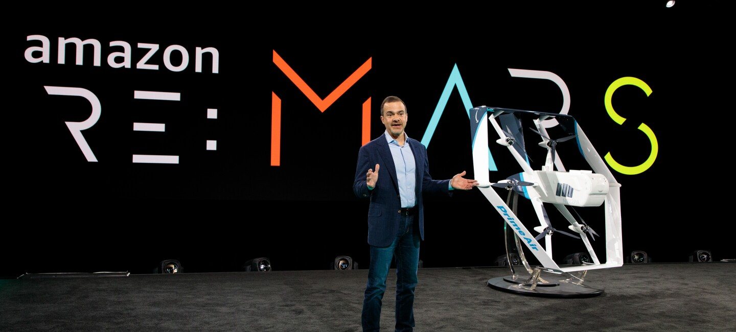 Jeff Wilke, CEO Amazon consumer worldwide, stands on a stage. Behind him is the re:MARS logo. To his left is a white and blue drone.