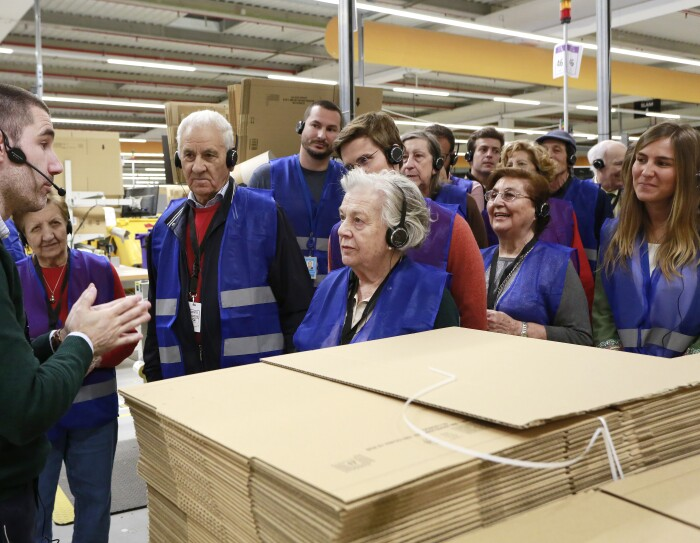 Detrás de unas cajas de Amazon se encuentra un grupo de personas mayores, abuelos, acompañados de su nietos, que escuchan atentamente las explicaciones del amazonian que les guía en su visita por el centro logístico.