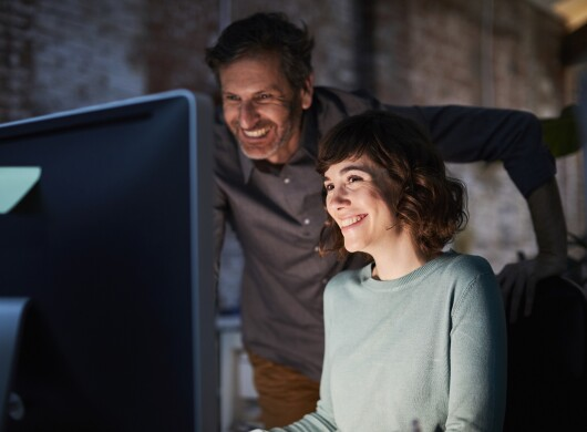 Man and woman looking at a computer screen. Both individuals are smiling. The light from the monitor lights their faces in an otherwise dark room.