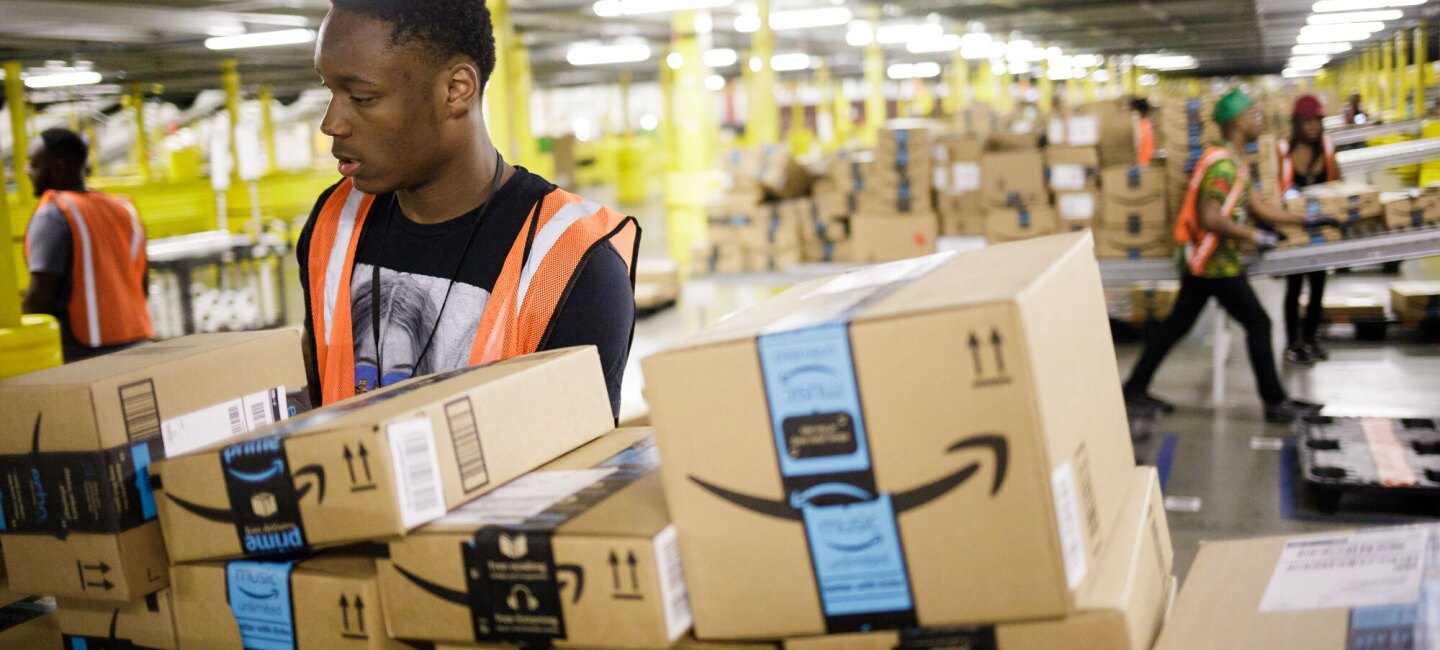 An Amazon associate wearing a t-shirt and orange safety vest prepares customer orders for shipment at an Amazon fulfillment center.