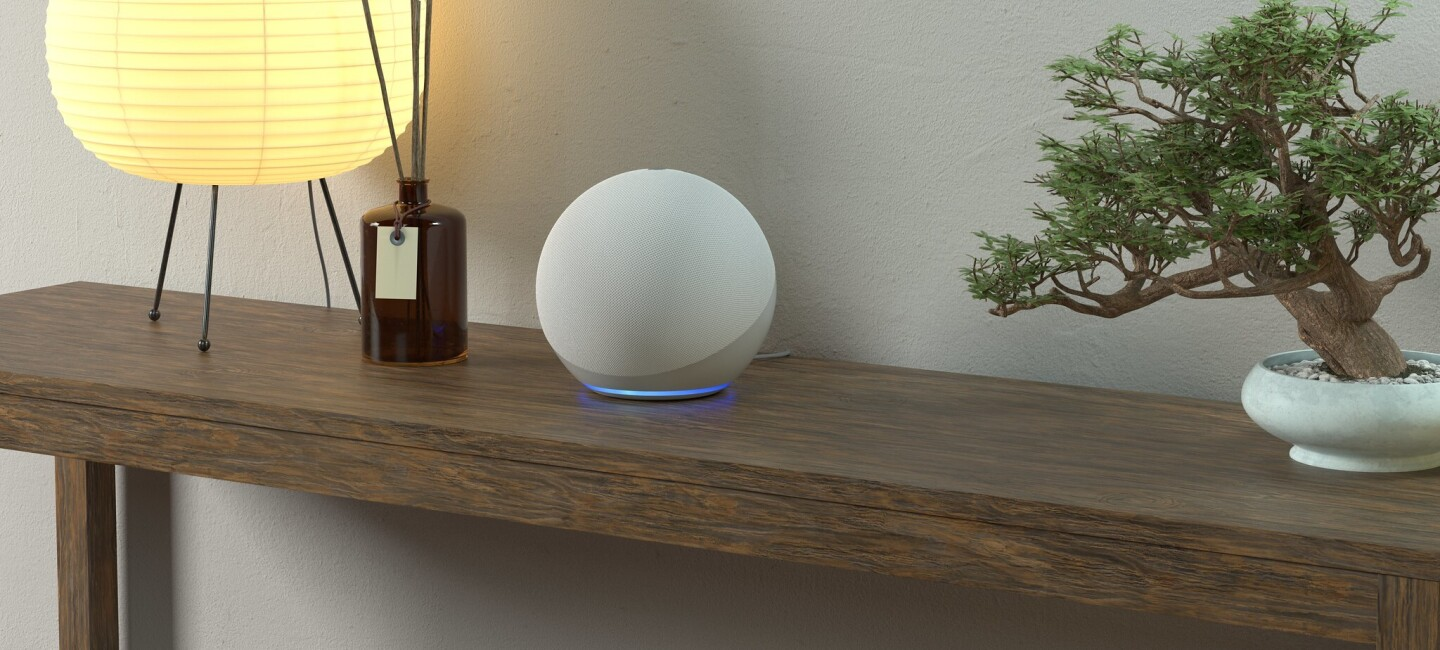 Echo Dot on a table next to a lamp, a reed diffuser and a bonsai tree.