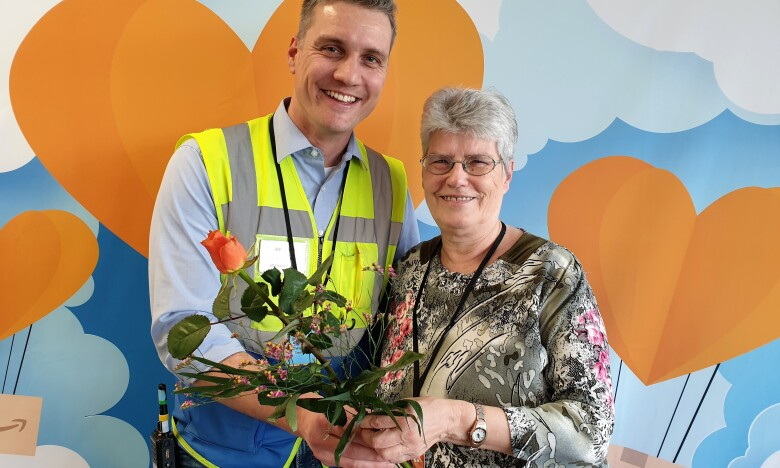 Ein Mann mit Sicherheitsweste überreicht einer älteren Dame eine Rose