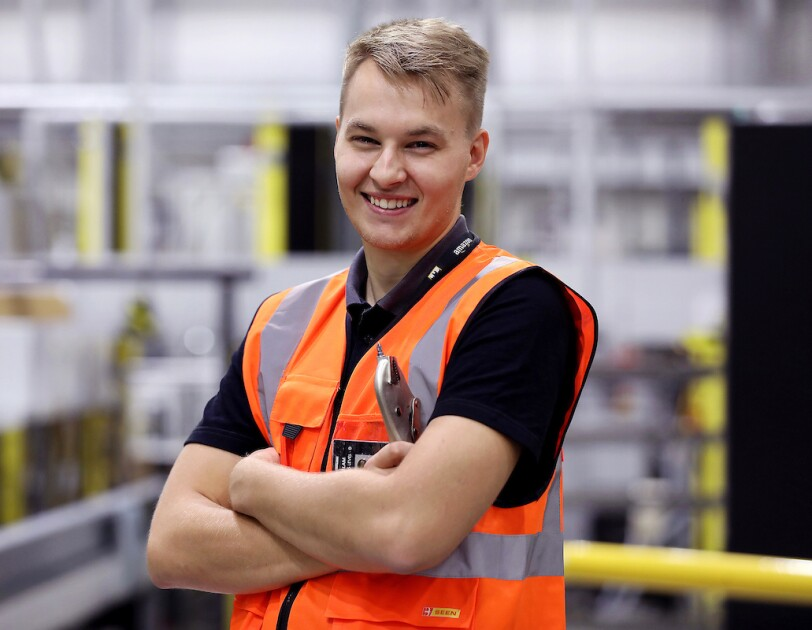 Mantas Budraitis, an AFE apprentice, standing with his arms crossed at the Peterborough fulfilment centre
