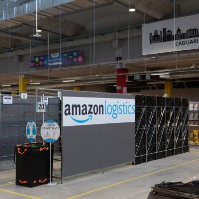 Foto di un'area di un magazzino Amazon. Su un pannello al centro si vede il logo di Amazon Logistics, mentre in fondo uno striscione con il profilo di una città e la scritta Cagliari